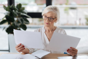 Successful businesswoman. Serious smart aged businesswoman holding two documents and comparing them while doing her job