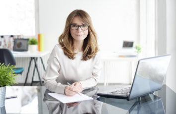 Shot of an attractive mature businesswoman doing some paperwork while working on her laptop in the office.