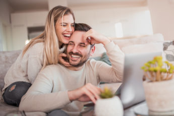 Close up of young couple working on laptop at home.