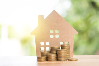 stack coins and house wood model with blur background, financial concept