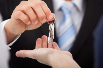 Cropped image of estate agent giving house keys to man in office