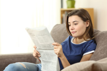 Portrait of a serious teenager reading a newspaper sitting on a couch in the living room at home