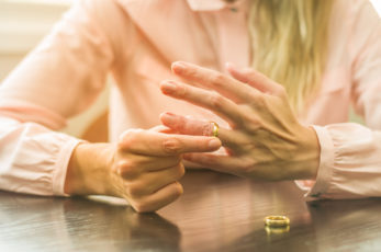 Great concept of divorce, ending of relationship, young woman pulling wedding ring from finger.