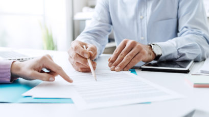 Business people negotiating a contract, they are pointing on a document and discussing together